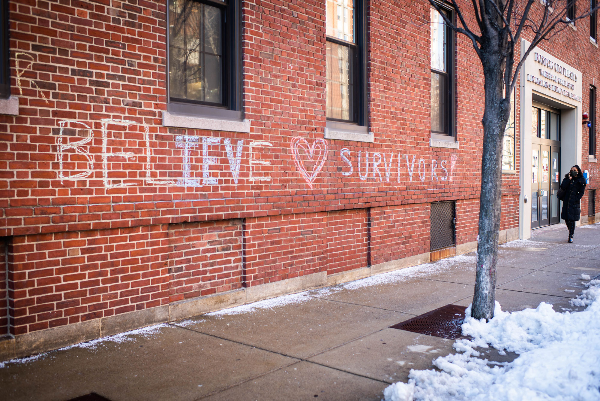 "A photo of chalk graffiti on the side of a brick building that reads ""Believe Survivors"""