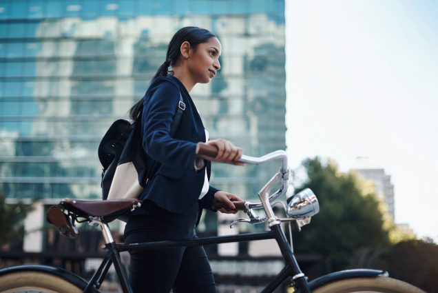 A photo of a woman wearing a business suit walking a bike. A cityscape is visible behind her.