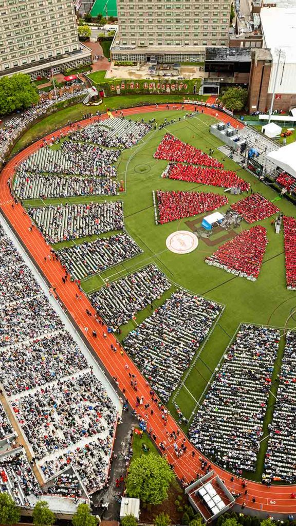 Aerial view of the 2019 Boston University Commencement on Nickerson Field on May 19, 2019. On the field, there are triangle and rectangular groups of people dressed in red on the right side of the field, then groups of white chairs, and gray bleachers furthest left.