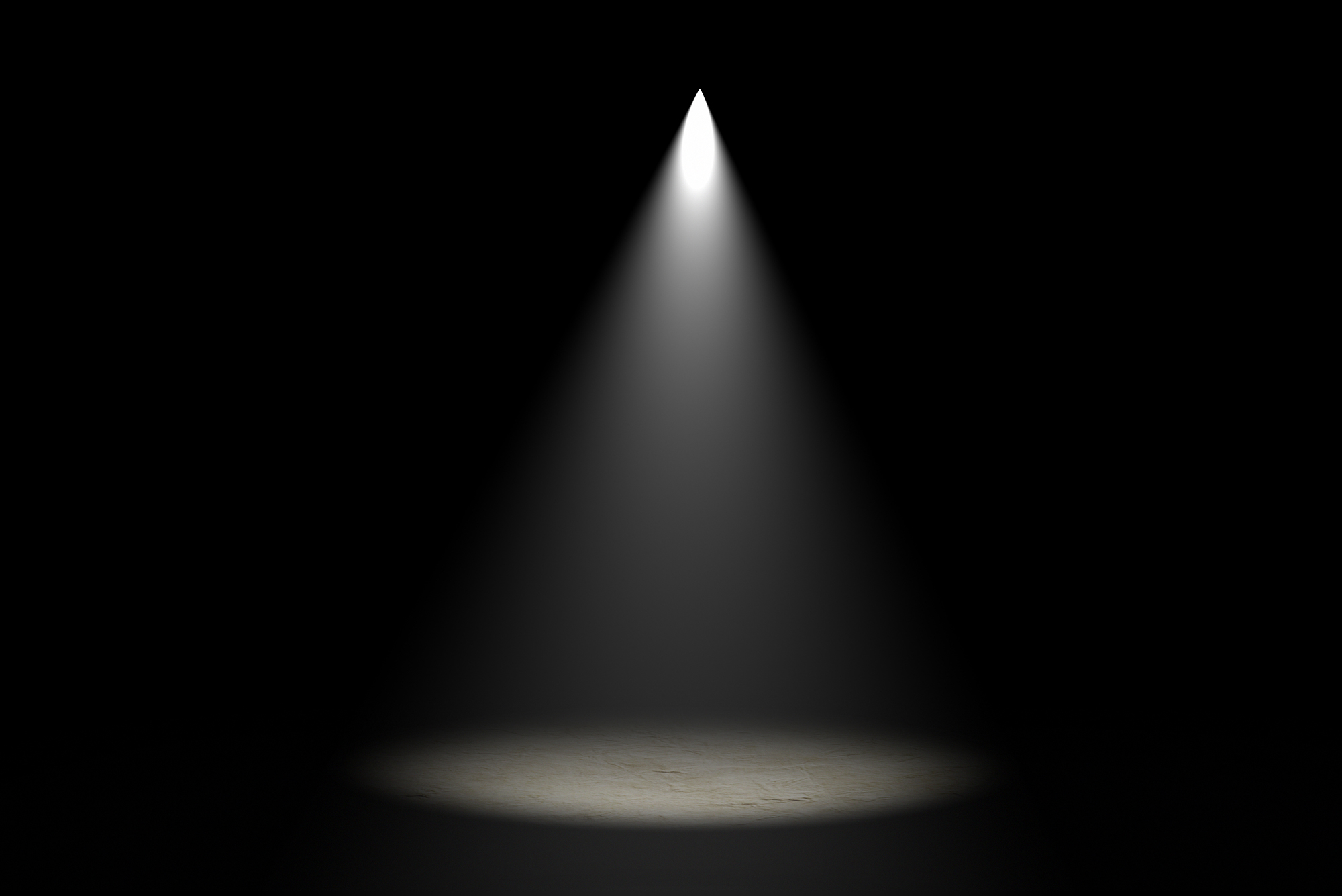 Photo of stage light shining directly down onto a stage in a completely dark room.