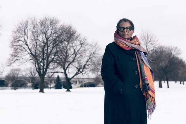 Photo of Henriquez, a middle-aged Black woman, standing in a long p-coat and colorful scarf in a snowy park.