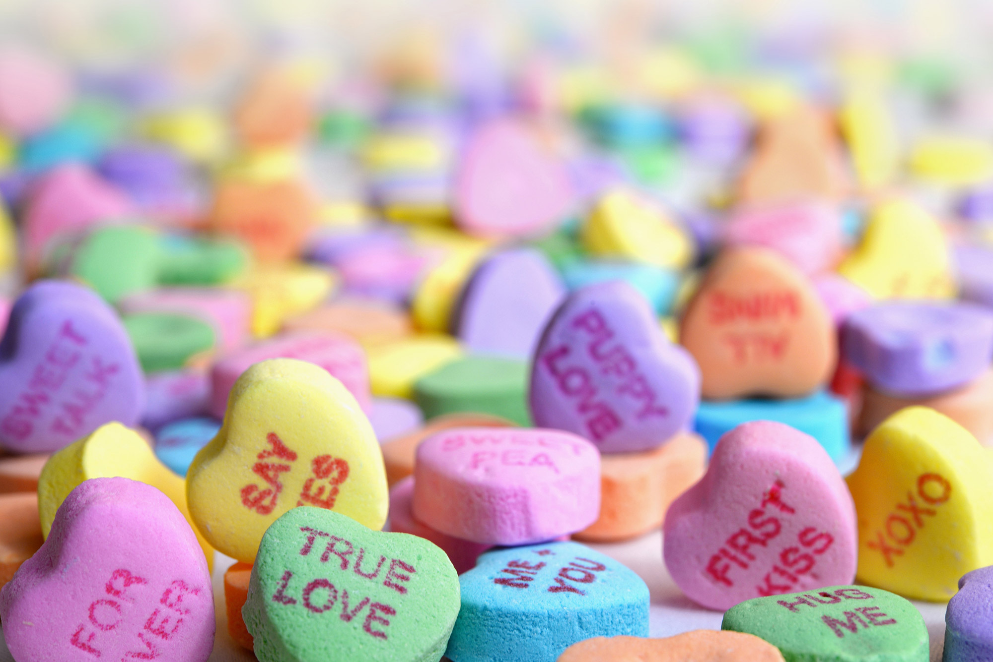 "Photo of a pile of colored candy hearts that read phrases like ""true love"" and ""say yes."""