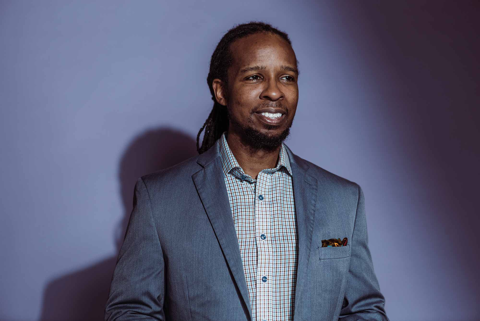 Portrait of Ibram X. Kendi standing in front of a lavendar background