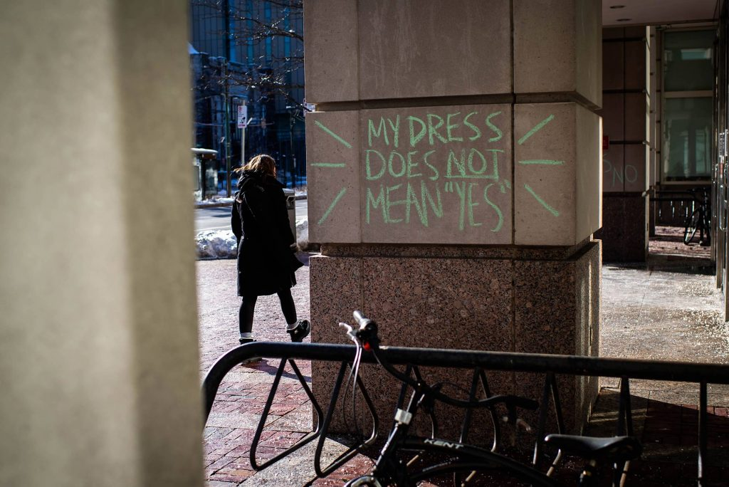 "Photo of green chalk graffiti is seen on a column of one of the buildings on campus on February 8, 2021. The graffiti reads ""my dress does not mean 'yes'"" with lines around it."