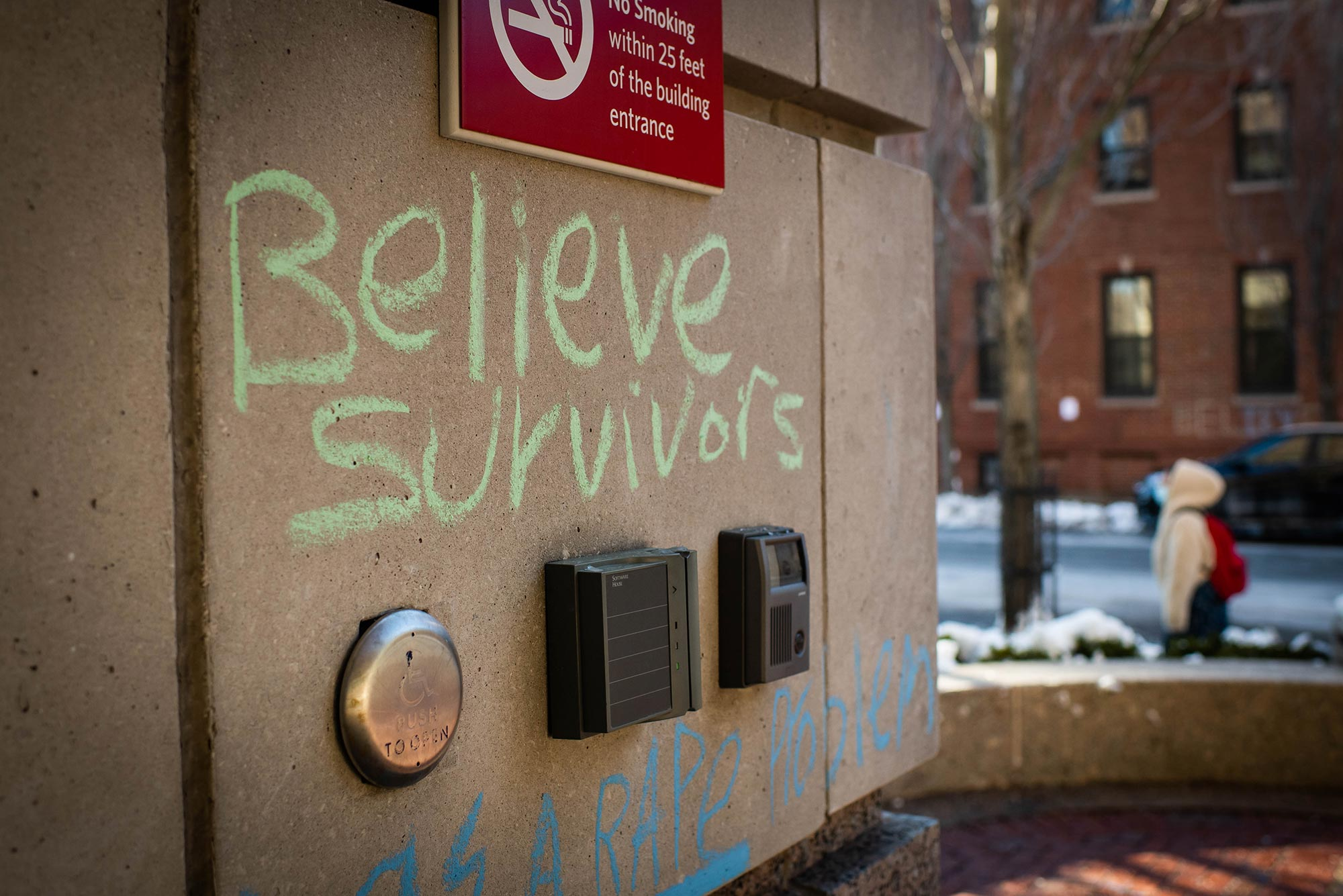 "Photo of green chalk graffiti is seen on a wall outside one of the buildings on campus on February 8, 2021. The graffiti reads ""believe survivors'"" with lines around it."