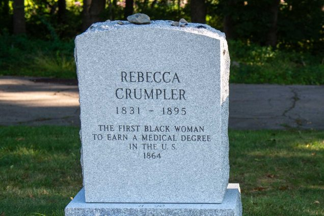 "Photo of the headstones of Rebecca Lee Crumpler (MED'1864), and reads ""the first Black woman to earn a medical degree in the US, 1831-1895"" The headstone is located in the Fairview Cemetery in Hyde Park, and surrounded by lush, green summer grass."