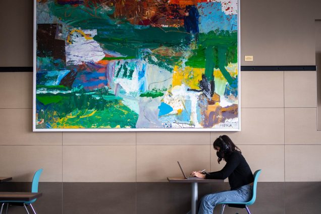 Photo of a student in a black shirt in jeans sitting alone at a table with a face mask on as they attend virtual class. A large abstract painting hangs on the wall behind them.