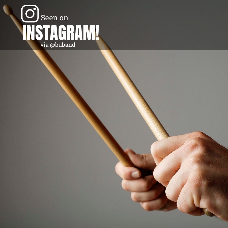 "Photo of a person's hands as they hold drum sticks, with a gray background. Overlay reads ""Seen on Instagram!"" via @buband"""