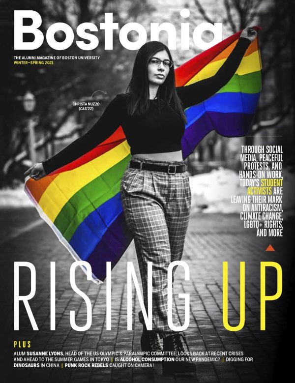 "Cover for the Winter-Spring 2021 edition of Bostonia magazine. The issue is called ""Rising Up"" and the cover has a black and white photo of a student activist extending a pride flag behind her; the photo has been edited so the colors are shining through."
