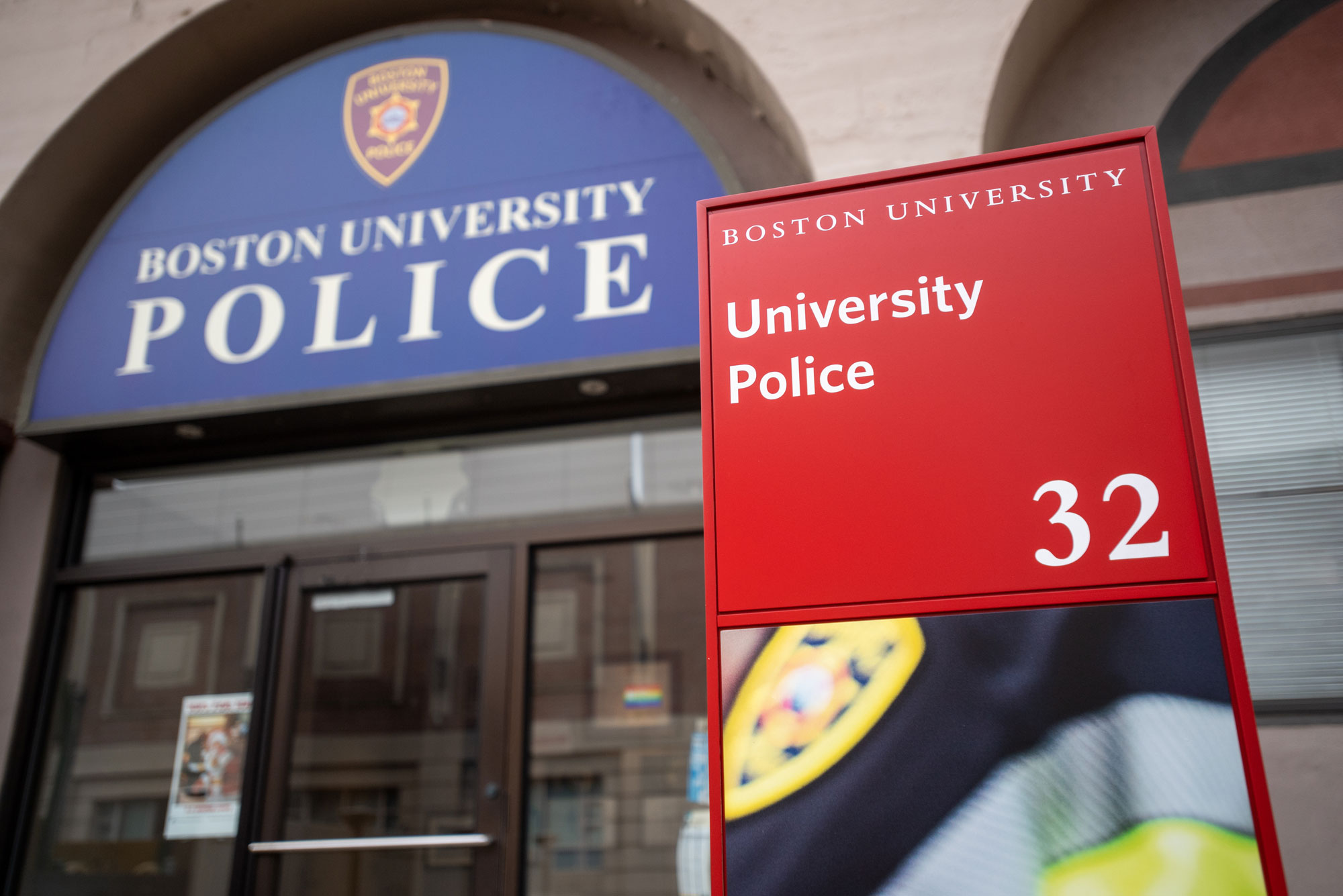 "A photo of the facade of the Boston University Police Department. A sign reads ""Boston University Police"" and an address placard reads ""Boston University, University Police, 32"""