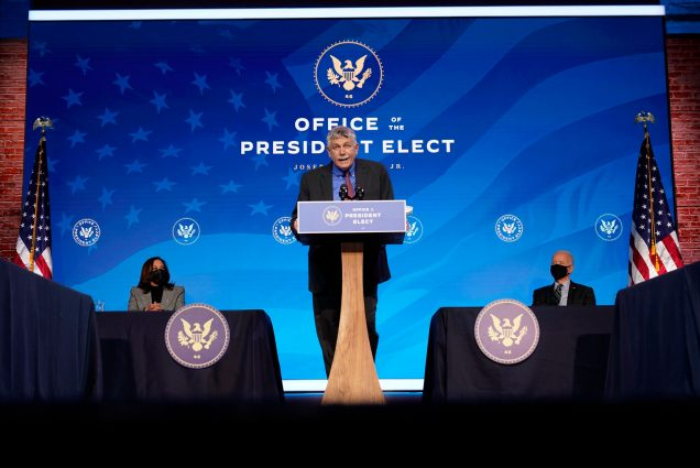"A photo of Eric Lander standing at a podium in front of a back drop that reads ""Office of the President Elect"""