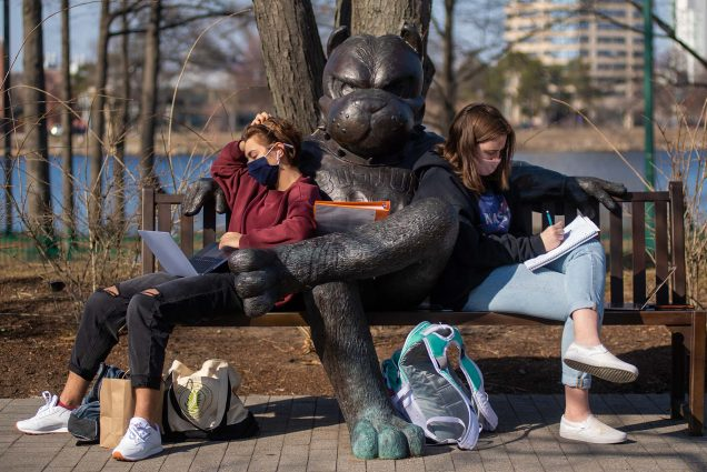 Photo of Alice Hotimski (CGS'22,CAS'24), left, and Eleanor Paul (CAS'24) get some work done in some beautiful 70 degree weather on March 11 as they sit on either side of the Rhett bench. They wear face masks and sit with their laptops and notebooks in their laps.