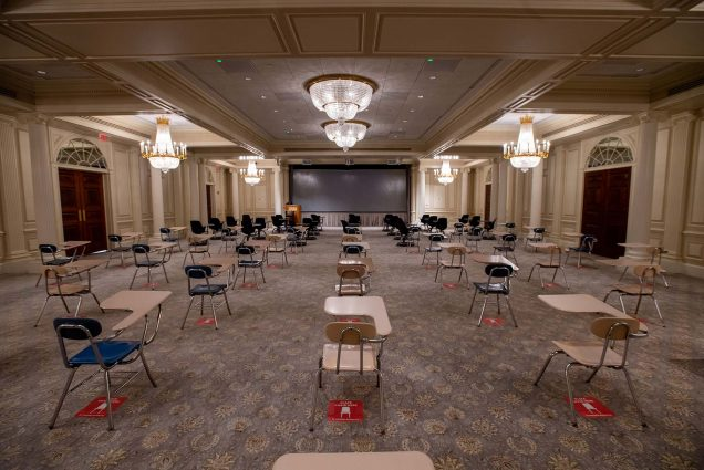 Photo of a classroom is set-up in one of the ballrooms at 1 Silber Way, the desks are spaced six feet apart and have red stickers underneath to indicate social distancing guidelines. Six fancy chandeliers hang from the ceilings.
