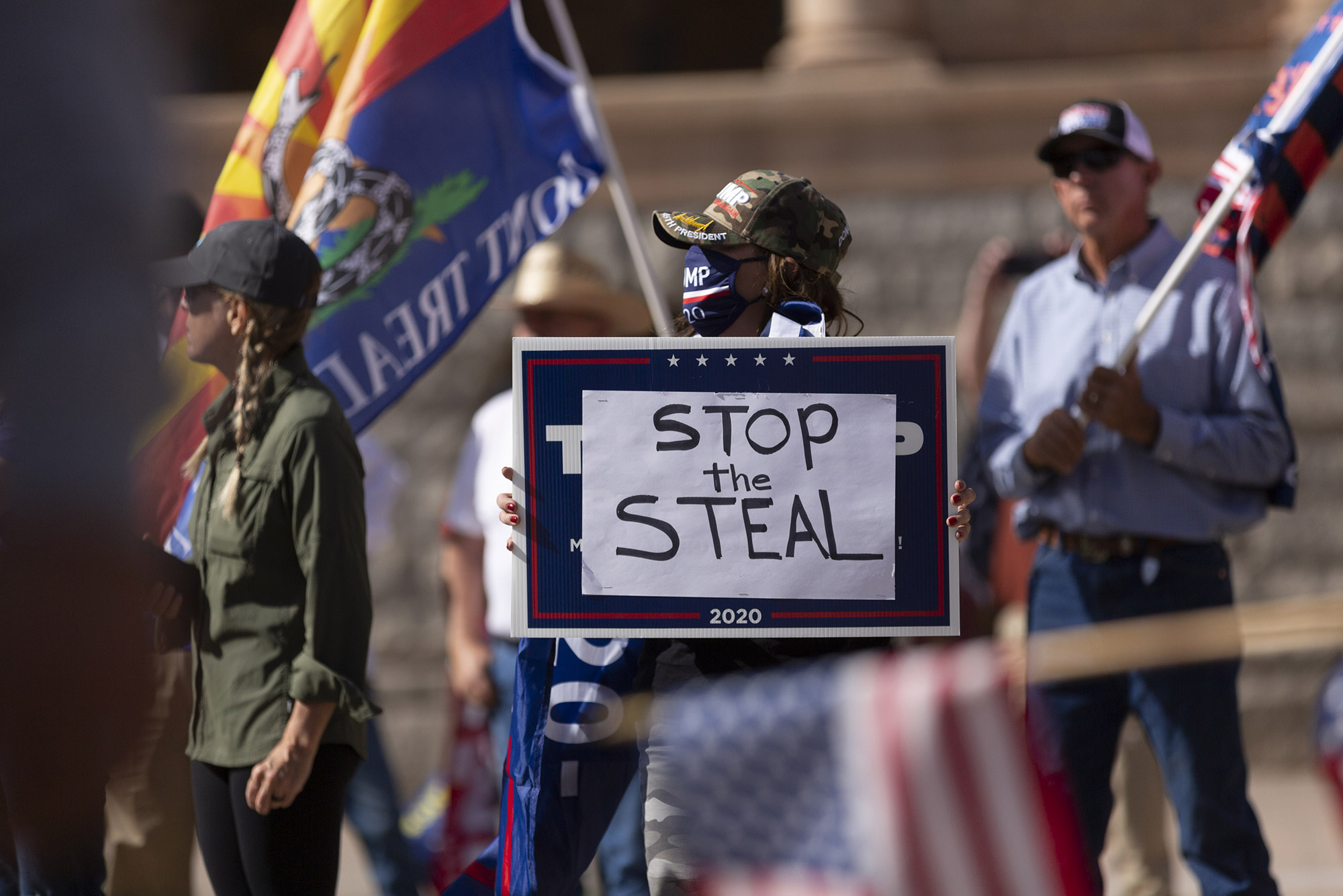 Photo of a 'Stop the Steal' in early November 2020. A group of people stand with 'don't tread on me' flags and American flags. In center foreground, a person in a camo baseball cap holds a sign with the words 'Stop the Steal'.