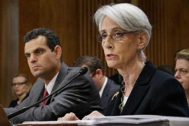 Photo of Wendy Sherman, when she was State Department Undersecretary For Political Affairs, testifying before the Senate Foreign Relations Committee about the ongoing P-5+1 talks with Iran during a hearing in the Dirksen Senate Office Building on Capitol Hill July 29, 2014 in Washington, DC. Sherman has white, ear-length hair and glasses, and speaks into a microphone at a desk with committee members seen blurred in the background.