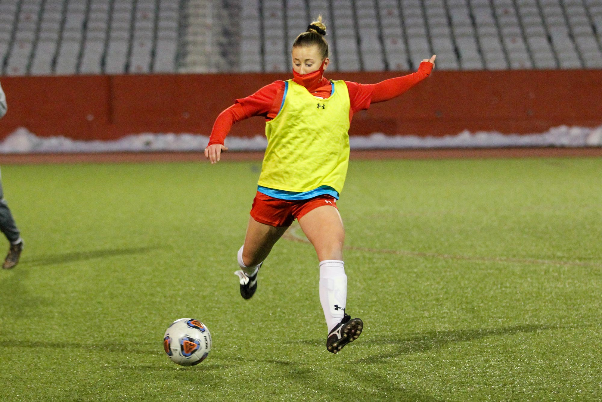 Photo of Ann Marie Jaworski (CAS'20, Wheelock'21) in a red long sleeve, shorts, and face mask, with a bright yellow practice pinny, about to strike a soccer ball. Empty bleachers and the foot of a team mate are seen in the background.