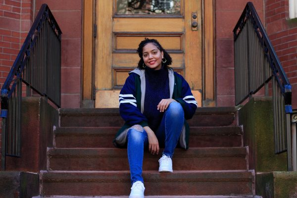 Photo of Solange Hackshaw (COM'21) in a stylish blue coat with white stripes on the sleeves sitting on the steps outside of a brown stone. We smiles, wears hoop earrings and rests her hands on her knees.