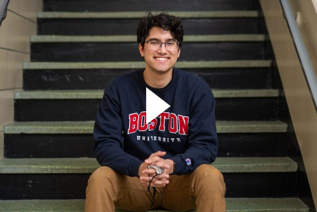 "Photo of student vlogger Amit Bhatia (Questrom'24) sitting on the steps of a staircase with a navy blue sweatshirt that says ""Boston University"" in red and white. He smiles and holds his face mask in his hands. A white video play button is overlaid."