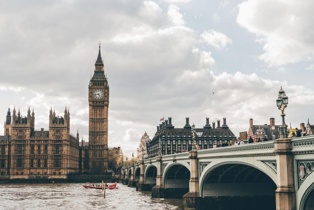 Photo taken from across the Thames River of Big Ben with an ornate bridge on the right; the heads of people walking over the bridge are seen. In the river, a small red boat with people moves to the left; the sky is grayish and cloudy.