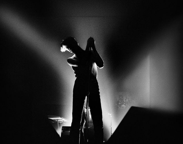 Black and white photo of Susan Ann Sulley of The Human League performing at Spit on Lansdowne Street in Boston. She stands at the mic with bright lights behind her but she's only seen in silhouette.