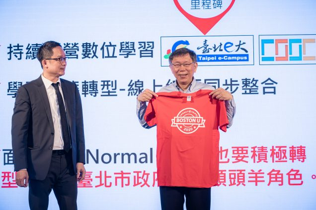 "Photo of Vincent Hsieh (LAW'92) (left) and Ko Wen-Je, the mayor of Taipei (right), who holds up a red t-shirt that says ""Boston U"" on it. Behind him, a large screen with Chinese characters is seen."