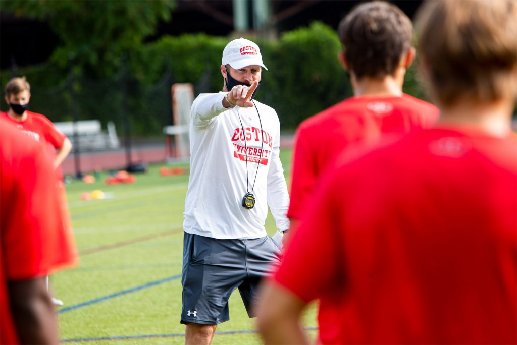 Photo of Kevin Nylen in a black face mask and white BU Athletics baseball cap and long sleeve pointing to members of the BU men's soccer who are seen from the back, blurred in the foreground in red shirts.