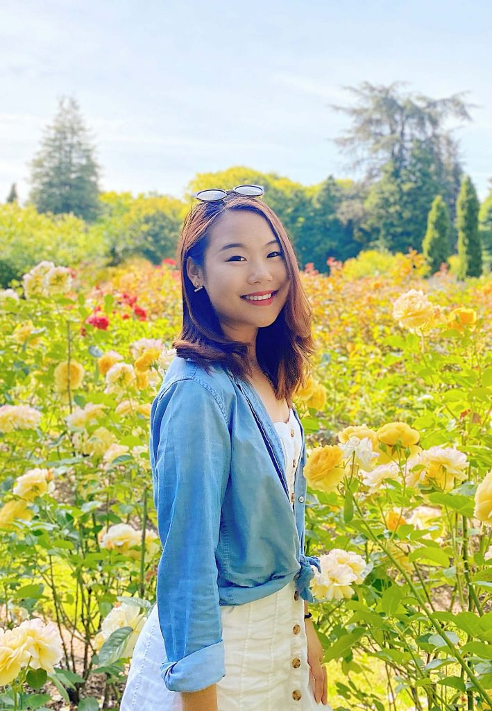 Photo of Migration Tales' cofounder Yiran Yu standing in field of flowers; she smiles and wears sunglasses on her head, a white dress and jean jacket.