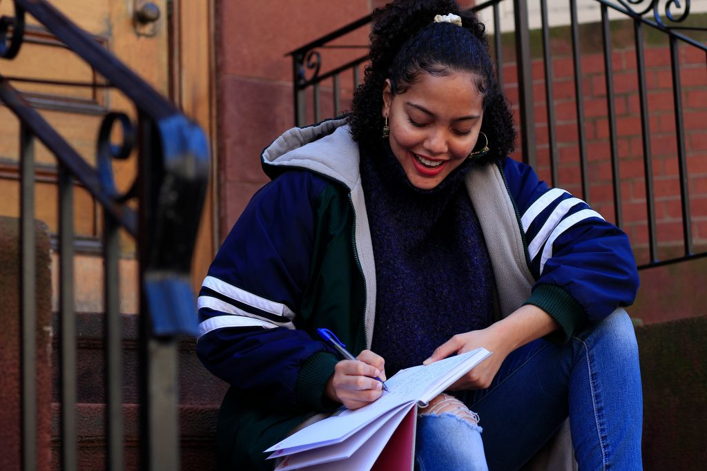 Photo of Solange Hackshaw (COM'21) in a stylish blue coat with white stripes on the sleeves sitting on the steps outside of a brown stone, smiling as she writes in a notebook.