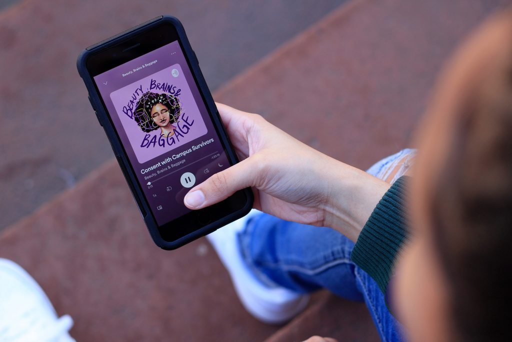 "Photo from above of a person holding a phone in their hand with Hackshaw's podcast, ""Beauty, Brains and Baggage"" on screen. The album cover of the podcast has an illustration of a smiling young black woman with colorful threads in her hair, with the text ""Beauty, Brains and Baggage"" written around her in purple."