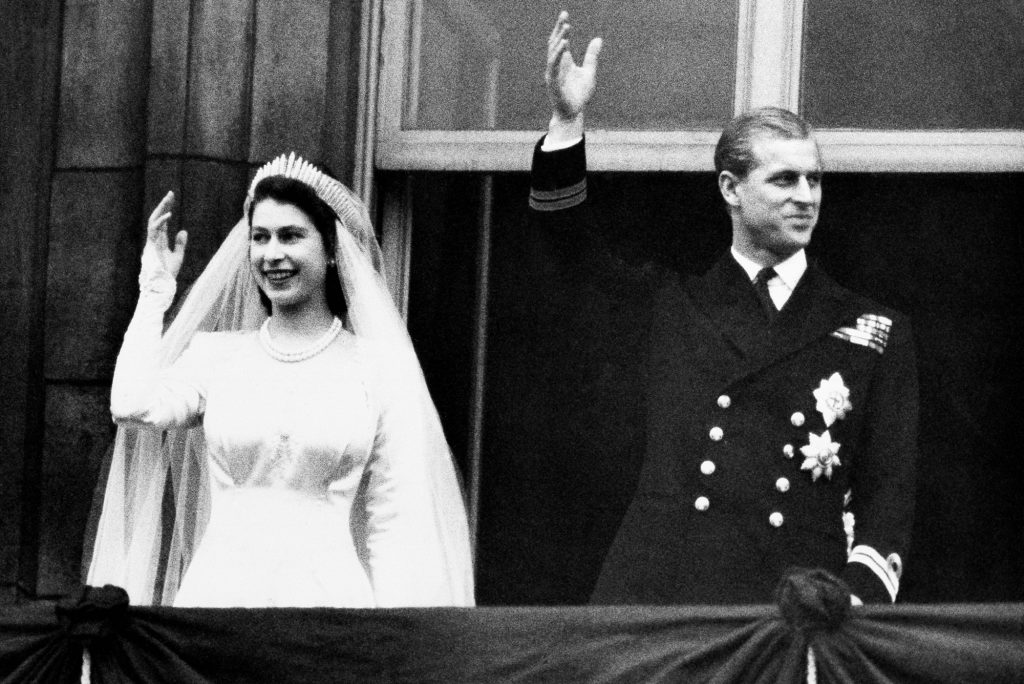 A photo of Prince Philip and Queen Elizabeth on their wedding day. They are waving from a balcony.