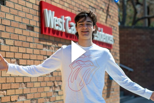 "A photo of Will Loggia with his arms outstretched standing in front of a brick wall with a red sign that reads ""West Campus Residences."" A video play button is overlayed."