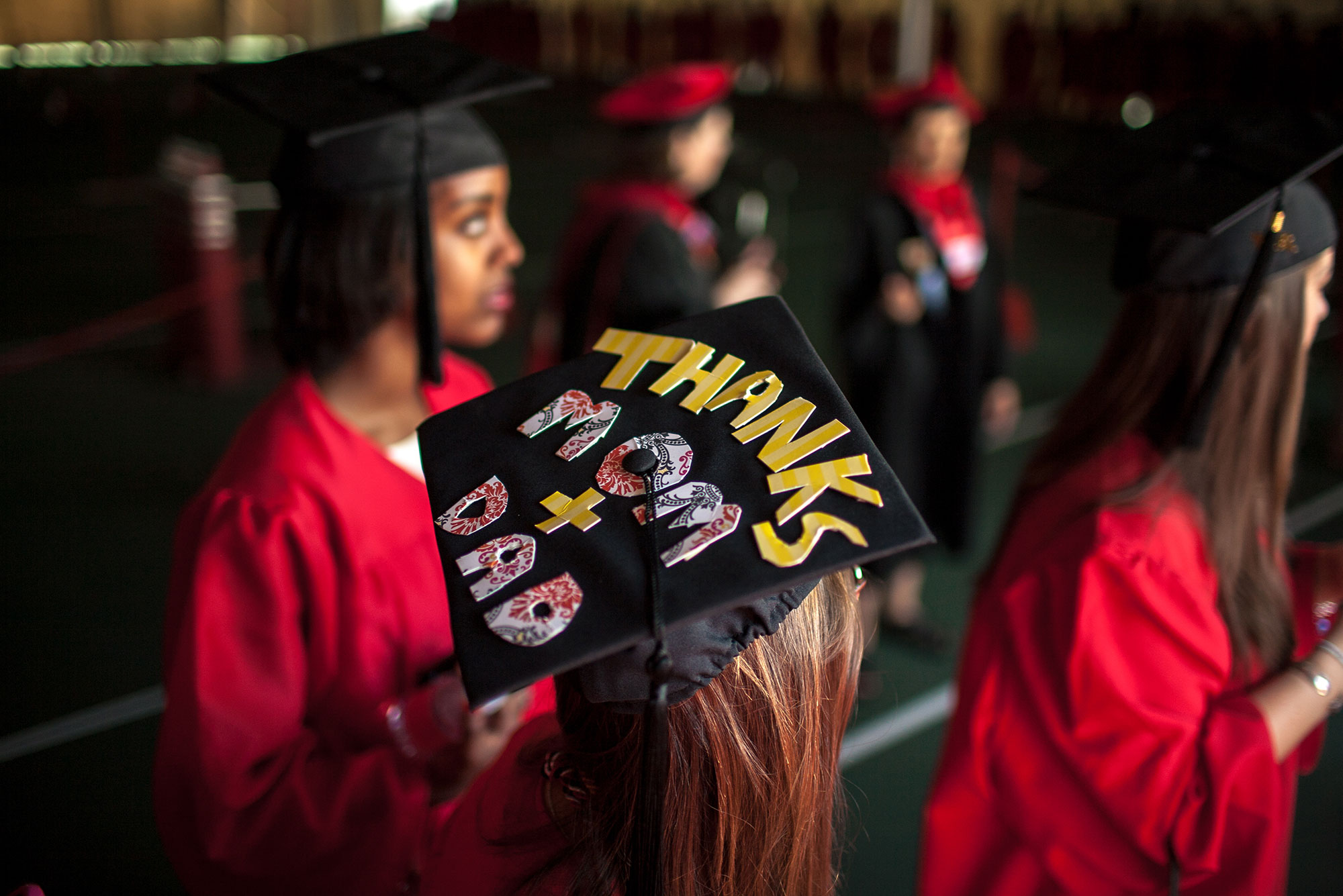 "Photo of a group of students in cap and gowns, one has a mortar board that reads ""thanks mom + dad"" in cut out letters."