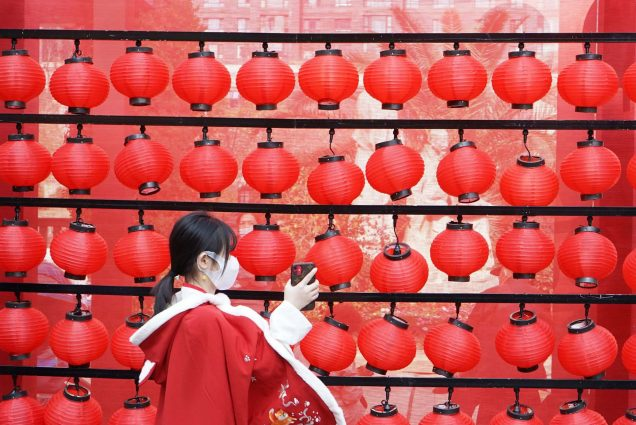 "Photo called ""New Year from Anywhere"" in which a young girl holds up her phone towards a wall of red lanterns; she wears a red coat with an intricate design."