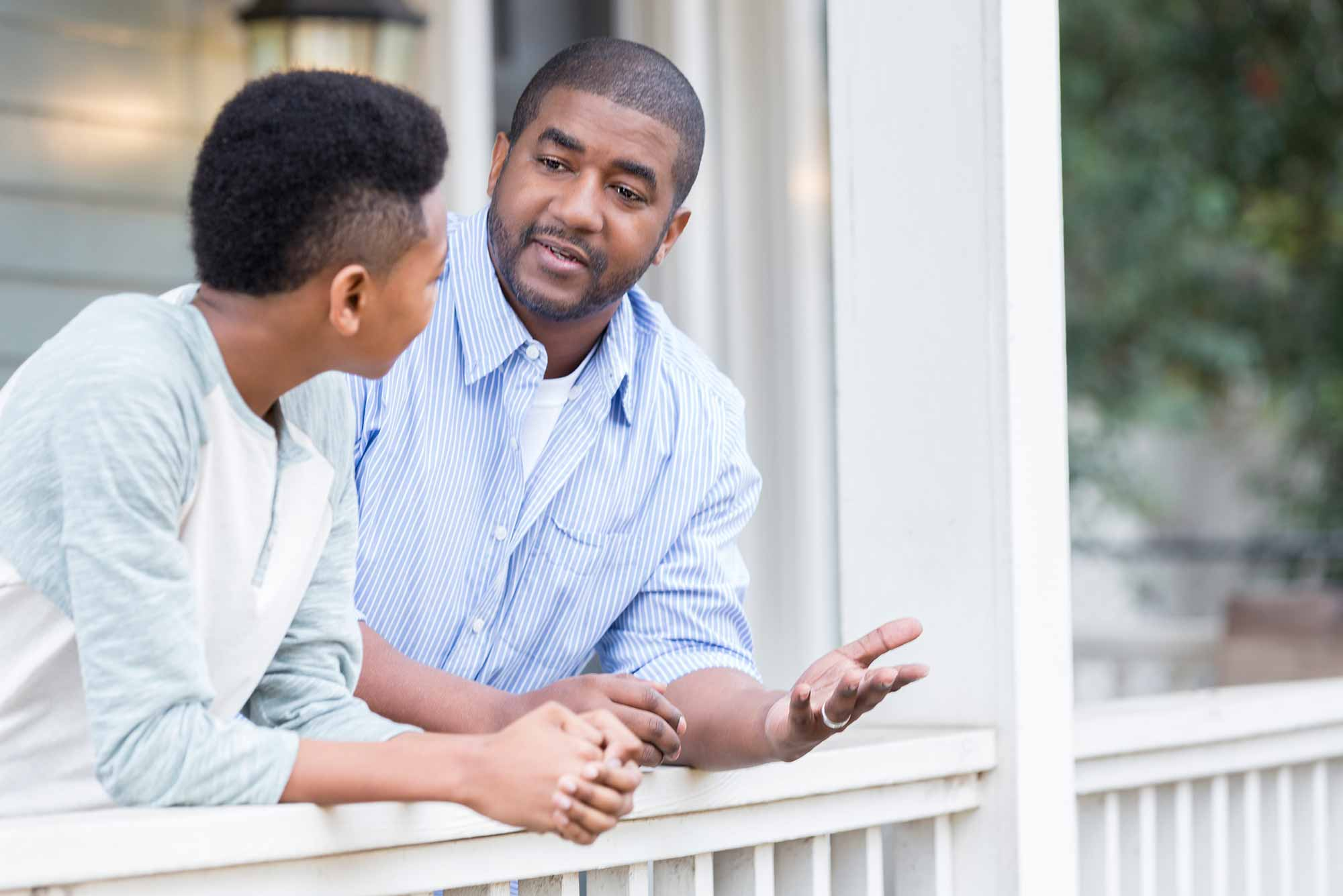 An African American father talks to his son