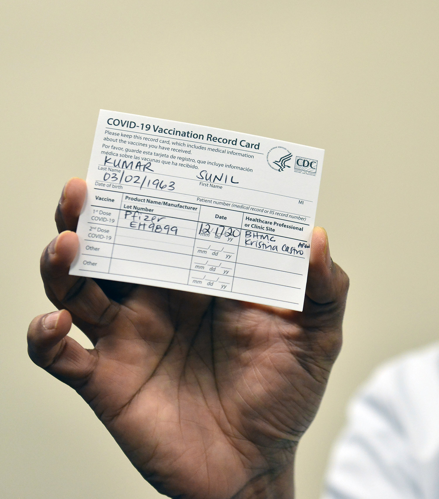 "Photo of someone holding up their vaccination card. It reads ""COVID-19 Vaccination Record Card….Last Name Kumar, First Name Sunil,"" and other personal information. They received the Pfizer vaccine. The background is beige."