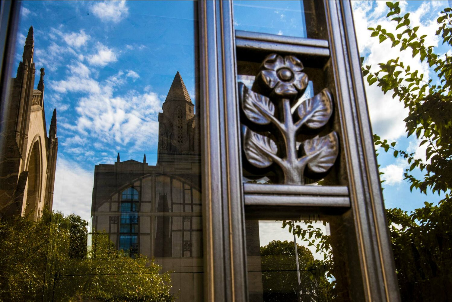 Photo of an ornate metal window grate with a flower design. Marsh Chapel and CAS are reflected in the window. The sky is bright blue and has a few clouds; a tree and other greenery is also reflected.