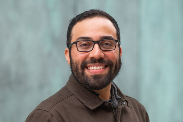 Headshot of Steve Ramirez, a CAS assistant professor of psychological and brain sciences, smiling in a brown button down, as he stands in front of a blue wall. He wears black glasses.