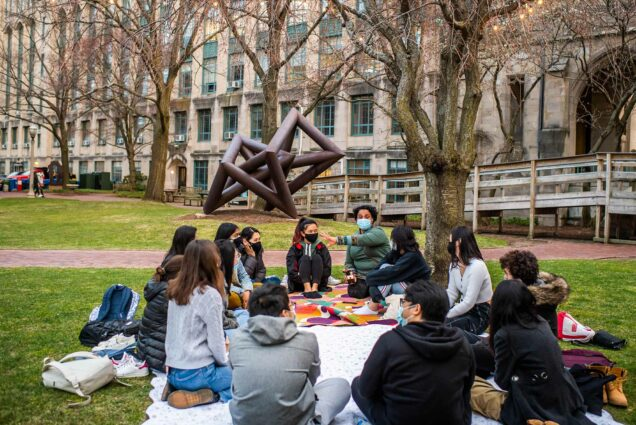Photo of Swati Rani teaching a writing class on Marsh Plaza on April 6, 2021. The class sits in a circle on blankets on the ground; they all wear face masks. Rani gestures as she speaks as the students listen and look towards her.