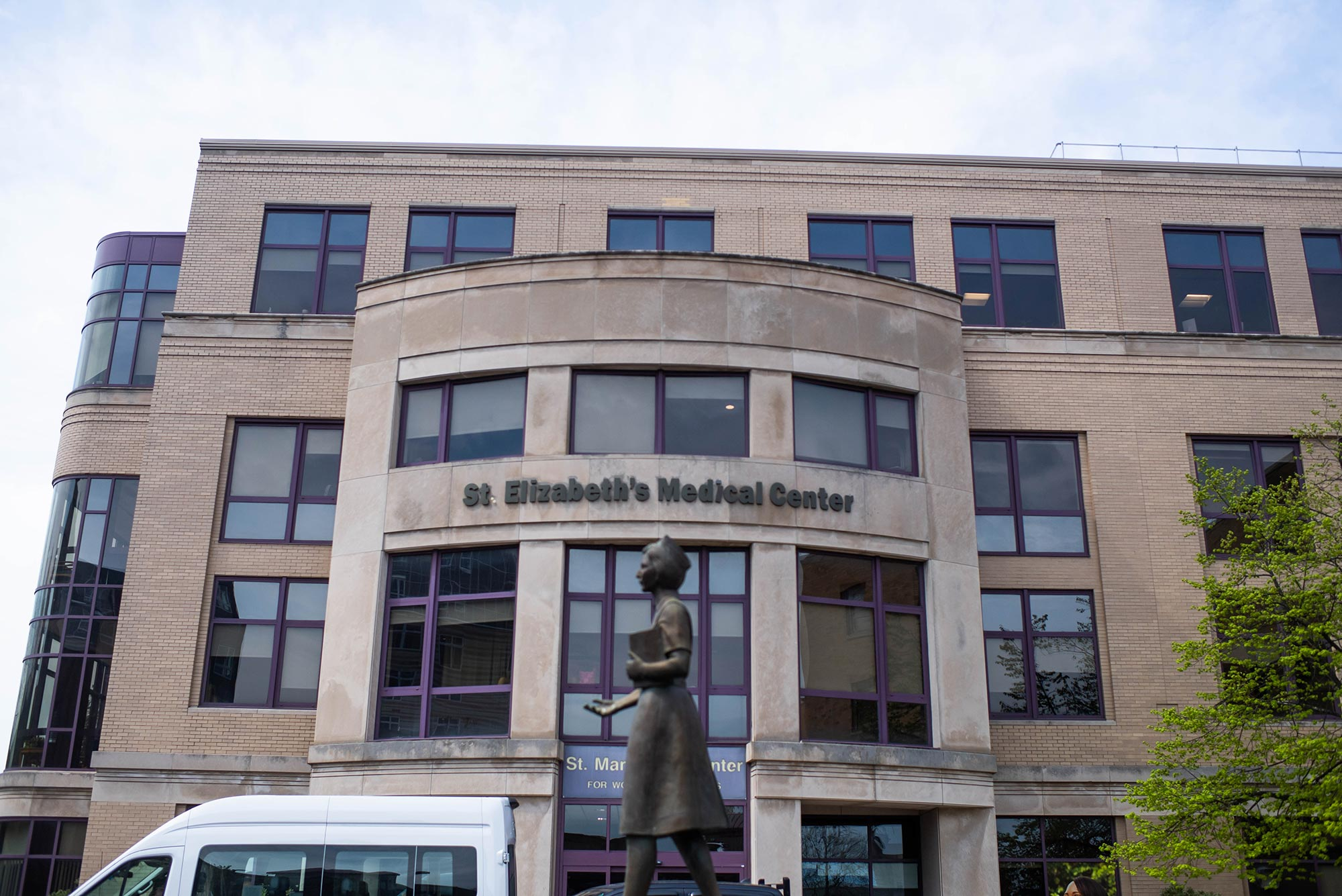 Photo of St. Elizabeth's Medical Center in Brighton, MA. At center, a statue of a woman in bronze is seen.