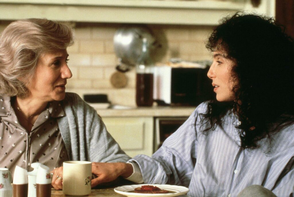 Still from the movie Moonstruck in which Dukakis, left, and Cher, converse at the kitchen table.