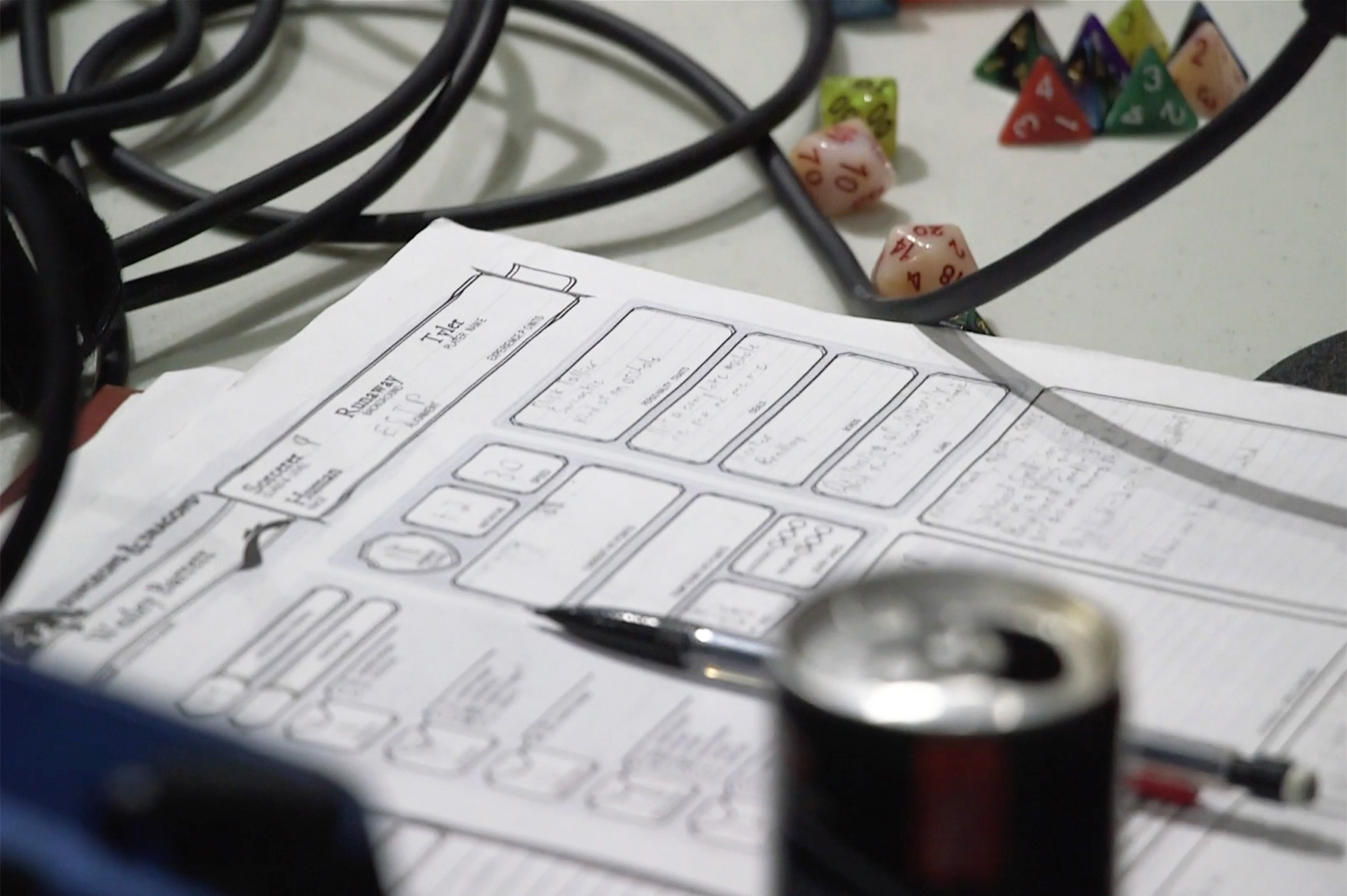 Image of a character sheet, die, mechanical pencil and microphone cords during a recording of the YMBWHWGH podcast. A blurred energy drink can is in the foreground on the bottom right.