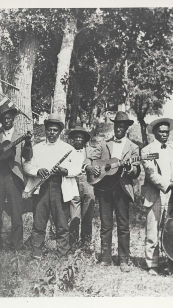 "Black and white photograph of a band of African-American playing at Emancipation Day celebration in June 19, 1900, held in ""East Woods"" on East 24th Street in Austin. There are 6 men in the band, they all wear suits and hats and hold their instruments, including a fiddle, guitar, clarinet, and upright bass. There are trees and an American flag hanging behind them."