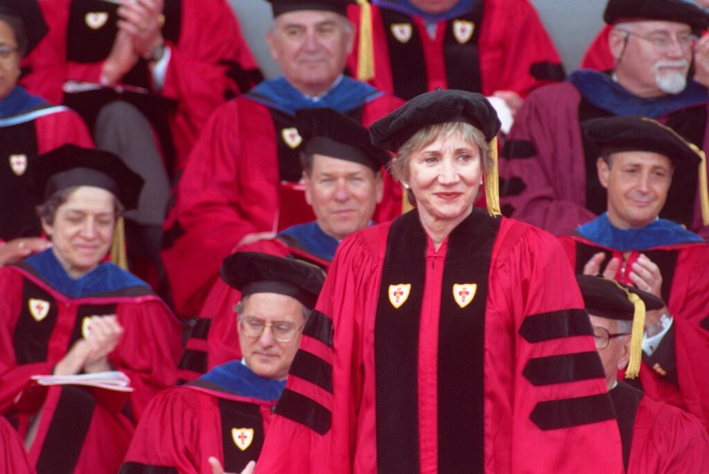 Photo of Olympia Dukakis receiving an Honorary Degree from Boston University in 2000. She wears a red gown and a black hat and smiles while looking off to her left.