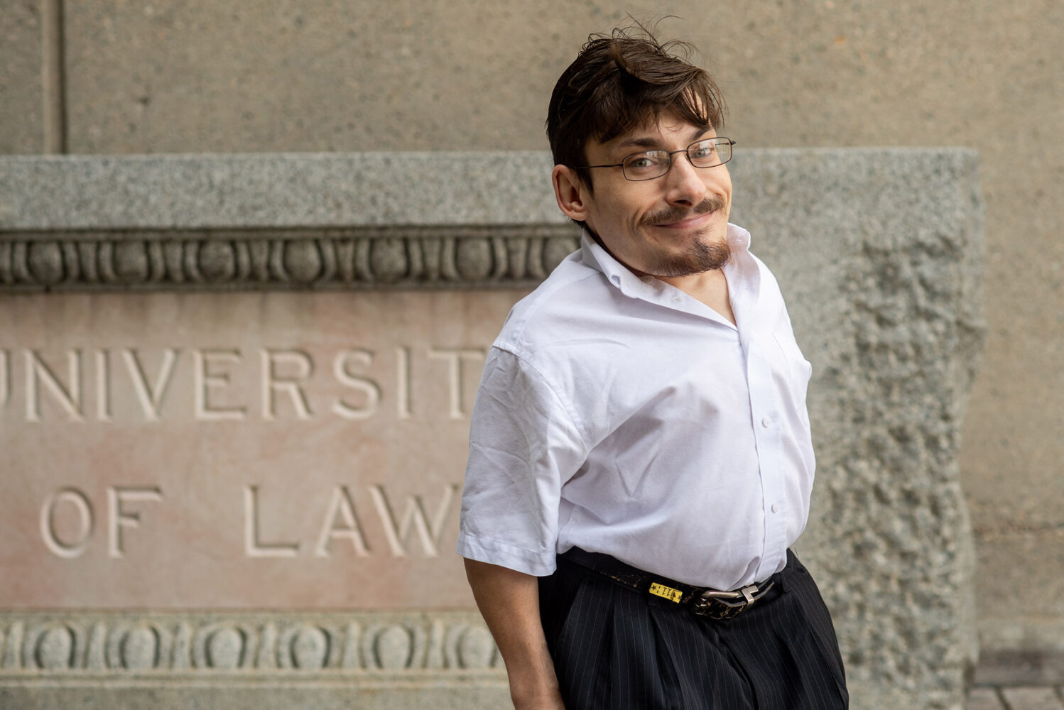 "Photo of Gaetano Mortillaro in a white button down, black pants and glasses. He smiles, standing outside one of the LAW buildings and a sign ""University Law"" is seen in the background."
