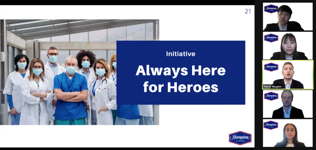 """Zoom screenshots of students presenting their marketing plan. The students are seen in formal attire on the right in individual zoom frames, and their slides are seen on the left. The slide has a picture of healthcare workers and reads """"Initiative: Always Here for Heroes"""""""