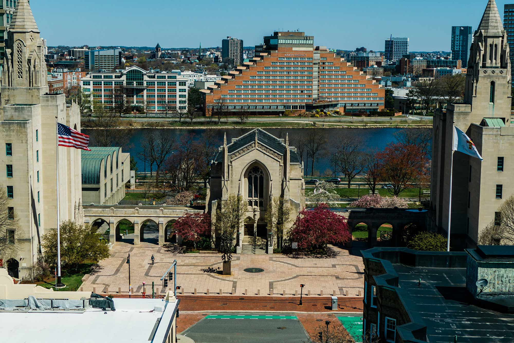 Drone shot of Marsh Chapel, Marsh Plaza, with hotel across the Charles River in the background. The plaza and street out front is empty.
