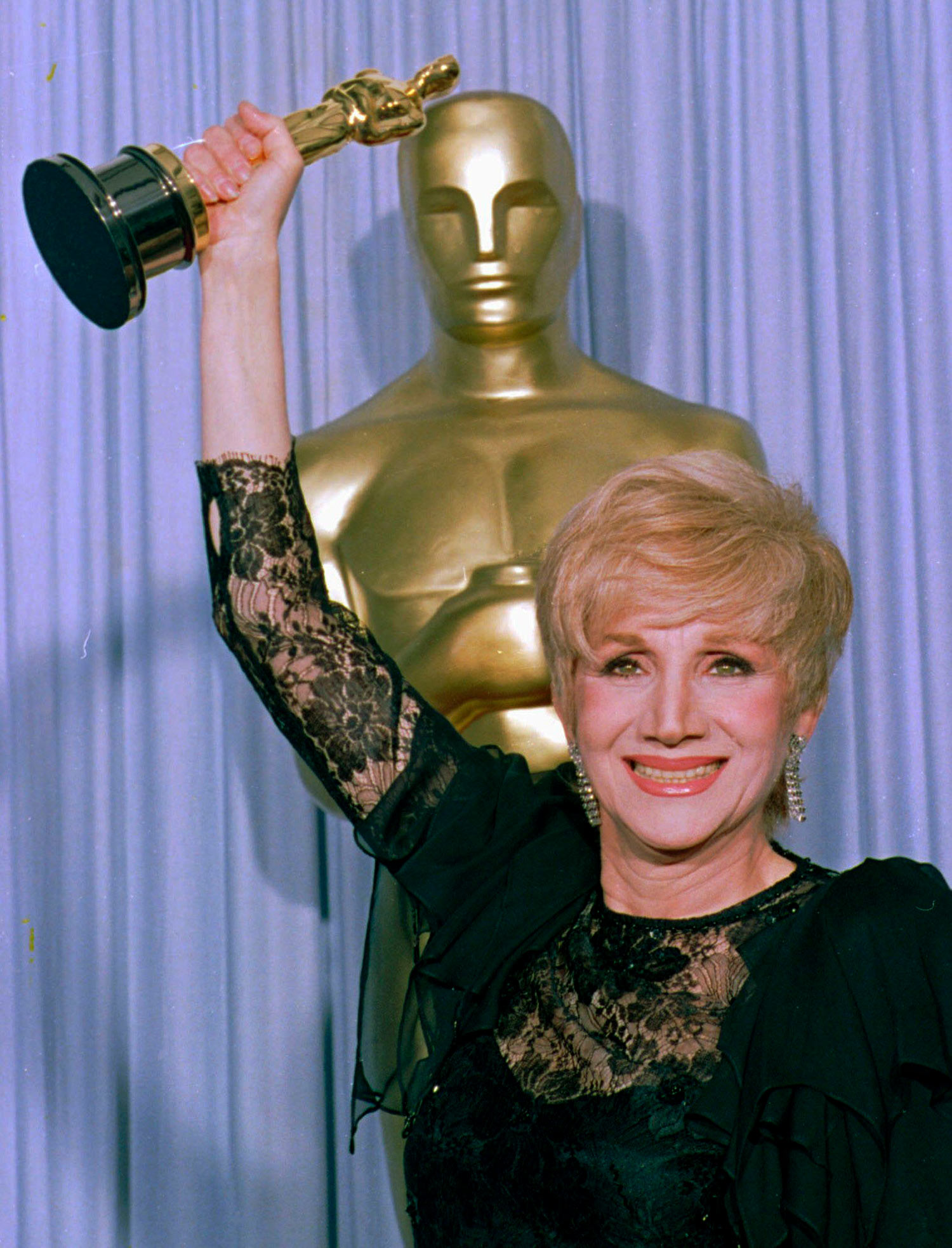 "Photo of Olympia Dukakis holding her Oscar at the Shrine Auditorium in Los Angles after being honored at the 60th Academy Awards as best supporting actress for her role in ""Moonstrck."" She wears a black, lacy gown and smiles brightly. Behind her, a large oscar statue and purple curtain are seen."