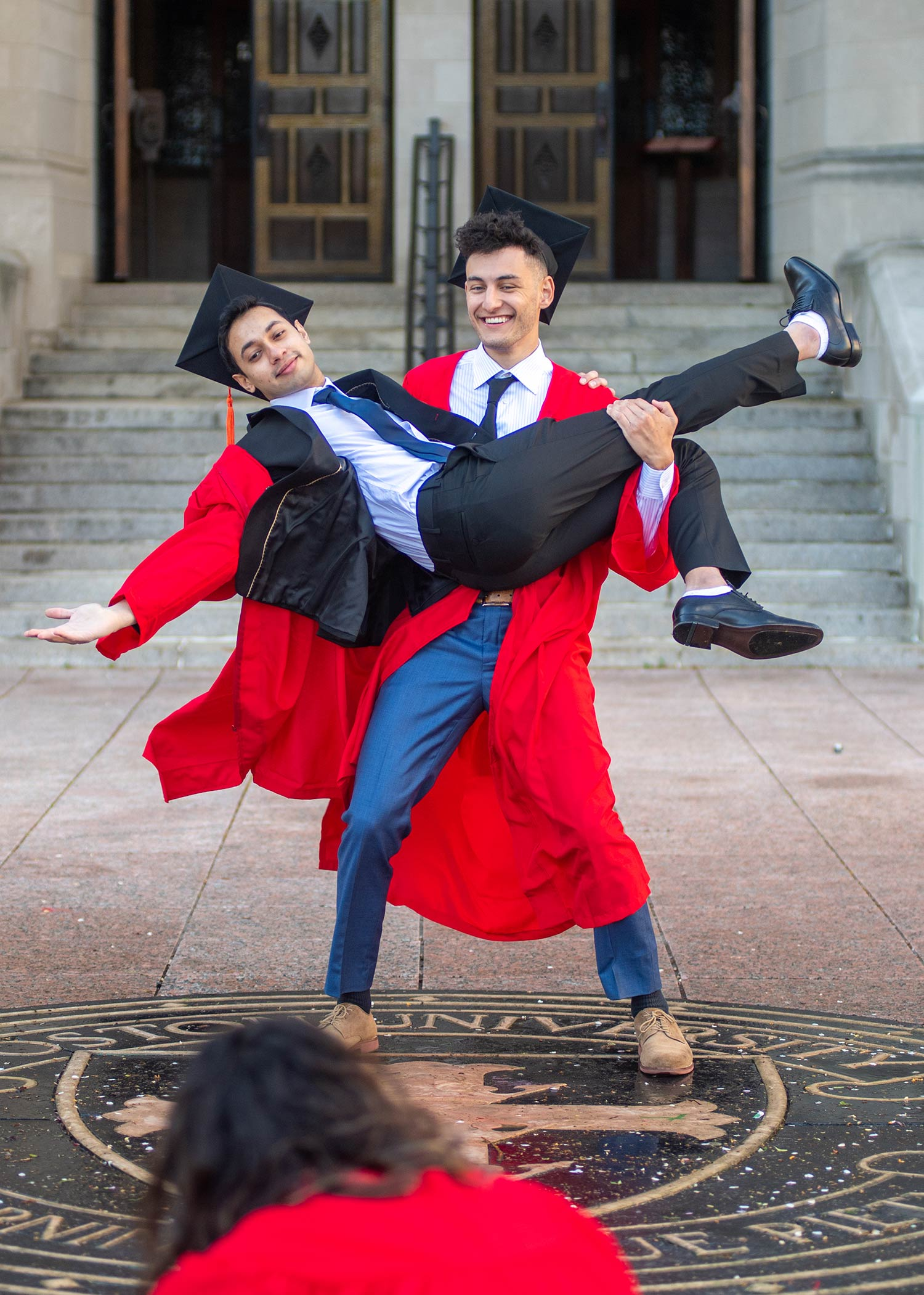 Photo of Mrinal Ghosh (ENG'21) with his arms and legs extended as Camden Kronhaus (ENG'21) holds him up over the seal in Marsh Plaza May 11. They both wear suits and their caps and gowns and smile.