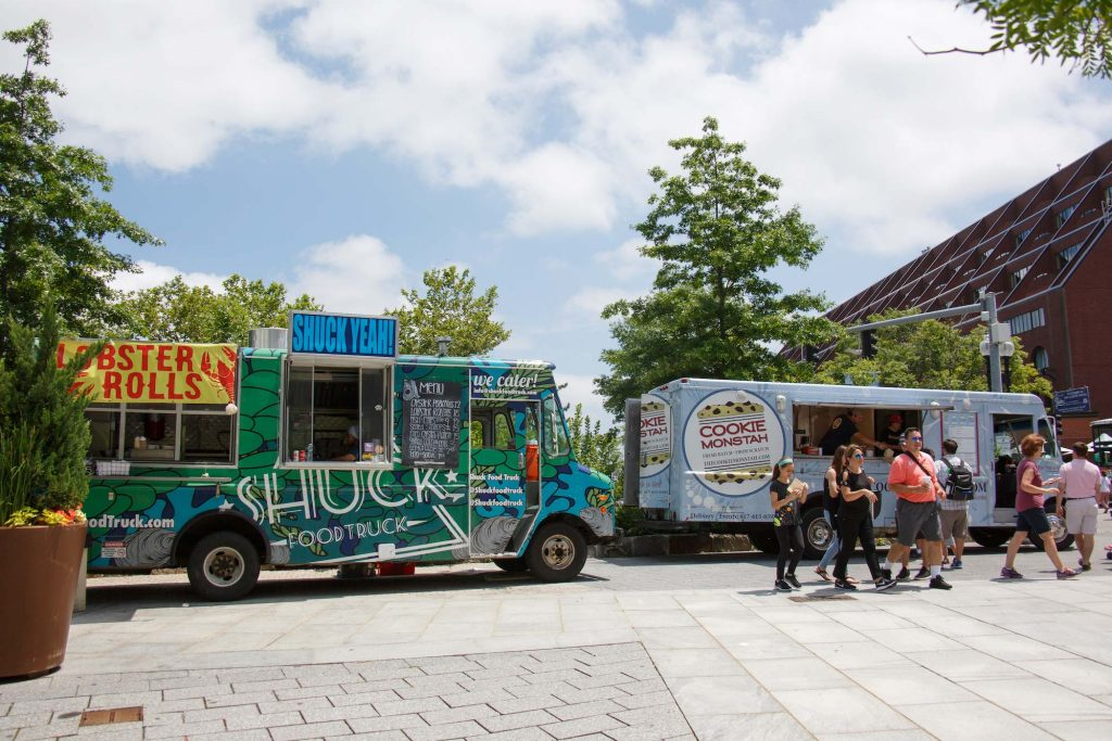 Photo of two food trucks parked along the Greenway, on the left, a green and blue truck with stripes called 'Shuck' is parked, while on the right, a light blue truck called 'Cookie Monstah' is parked. People stand and walk by in front of the latter.