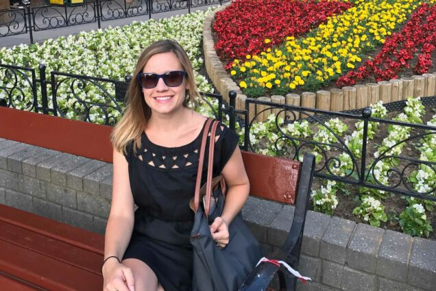 Photo of Carrie O'Connor during one of her many trips abroad. O'Connor was a BU lecturer in French who was killed Monday in an elevator accident. In the photo, she wears sunglasses and smiles on a bunch near a garden of flowers.